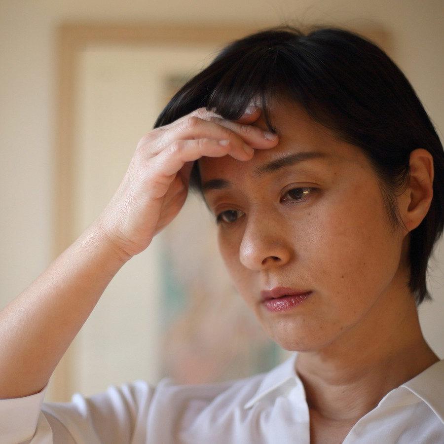 頭痛に悩んでいる女性