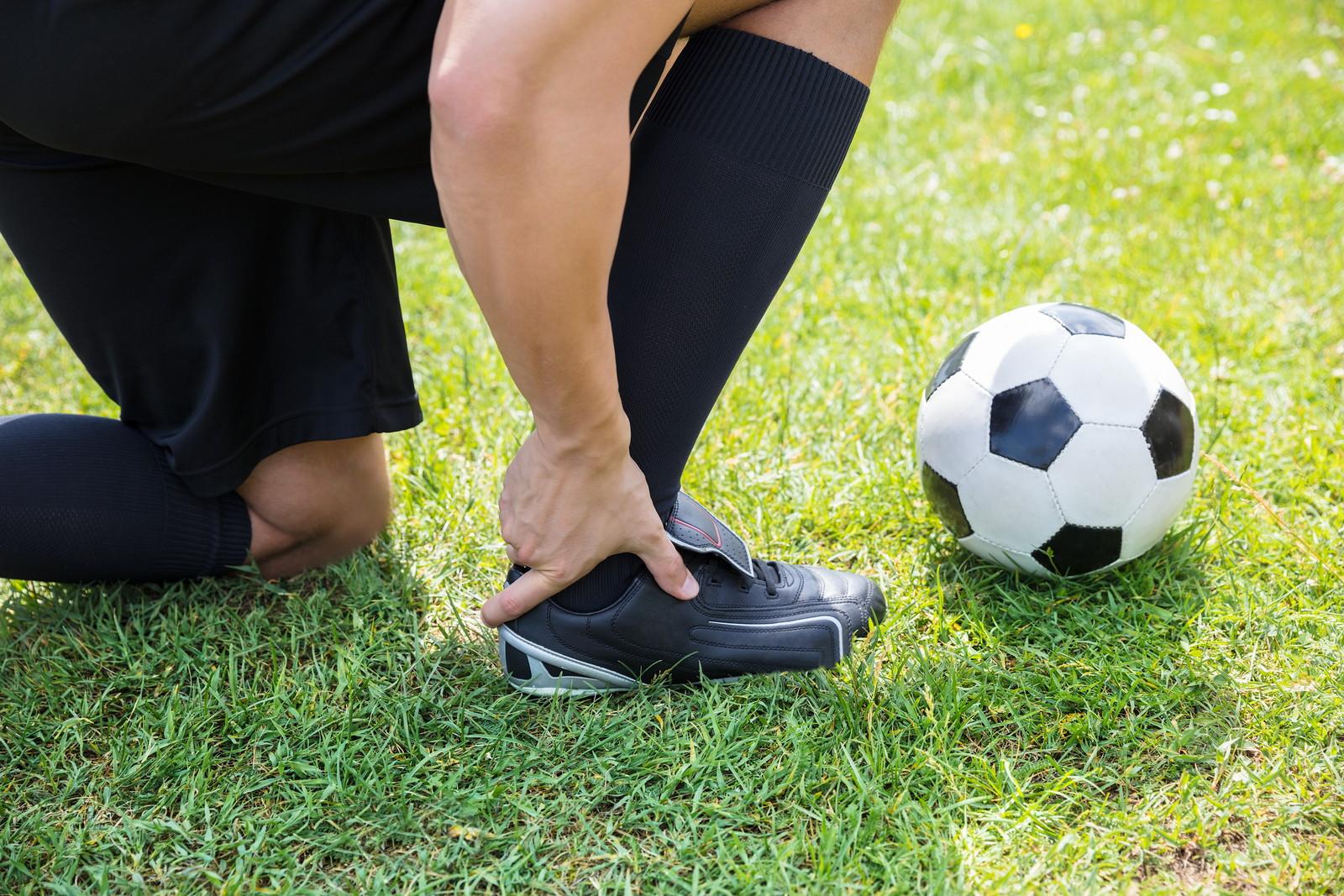 足首を抑えたサッカー選手